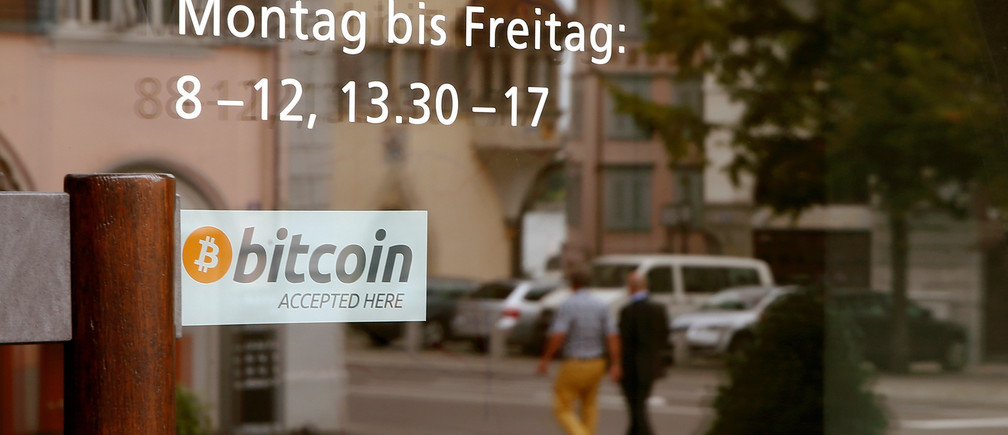 """A sticker reading """"Bitcoin accepted here"""" is placed at the entrance of the Stadthaus town hall in Zug, Switzerland, August 30, 2016. Picture taken August 30, 2016.  REUTERS/Arnd Wiegmann  - RTX2OLTZ"""