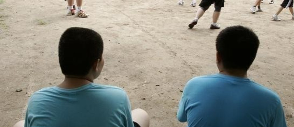 Boys watch their colleagues play at OK Slim summer camp on the outskirts of Beijing August 3, 2006. Some 40 obese children stayed in the camp for 30 days to lose weight at a cost of 6,600 yuan (825 US dollars) on average. The Ministry of Education statistics last year showed that 11.5 per cent of urban Chinese boys aged 7 to 22 were obese, and so were 8 per cent of urban girls of the same age group, China Daily reported.         REUTERS/Claro Cortes IV    (CHINA)