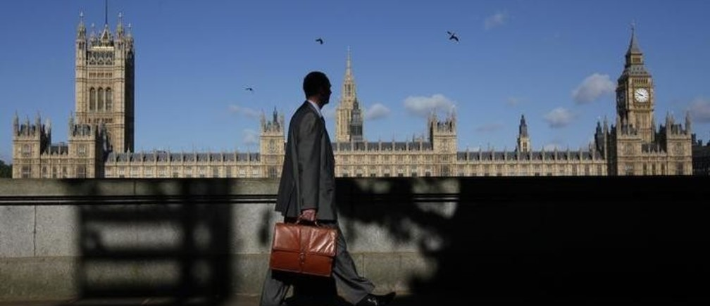 A man walks past the Houses of Parliament in London May 10, 2011. The Palace of Westminster, inside the Houses of Parliament, could host wedding receptions under plans to cut Parliament's subsidised catering bill, local media report. REUTERS/Suzanne Plunkett (BRITAIN - Tags: TRAVEL CITYSCAPE POLITICS)