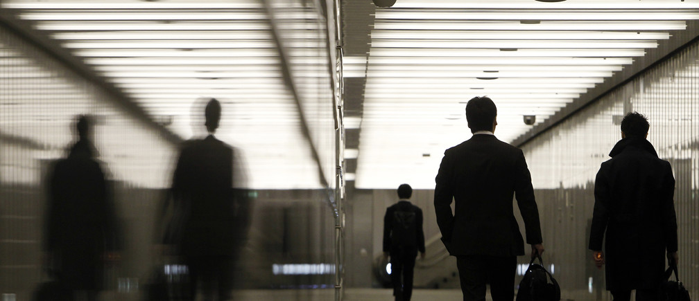 Businessmen walk through a business complex in Tokyo January 11, 2011. Japan's index of coincident economic indicators rose a preliminary 1.4 points in November from the previous month, the Cabinet Office said on Tuesday, up for the first time in three months. REUTERS/Yuriko Nakao
