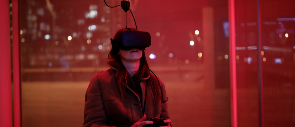 A woman plays a video game with the Oculus Rift VR in Paris, France, December 2016.