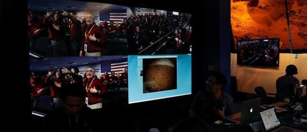 The mission control team at NASA's Jet Propulsion Laboratory (JPL) react on a video screen as the spaceship Insight, NASA's first robotic lander dedicated to studying the deep interior of Mars, sends its first picture back to JPL, in Pasadena, California, U.S. November 26, 2018. REUTERS/Mike Blake - RC1211C65800