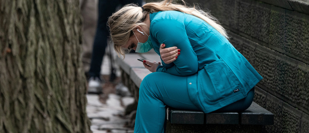 A healthcare worker sits on a bench near Central Park in the Manhattan borough of New York City, U.S., March 30, 2020. REUTERS/Jeenah Moon     TPX IMAGES OF THE DAY - RC2NUF9VY5KU