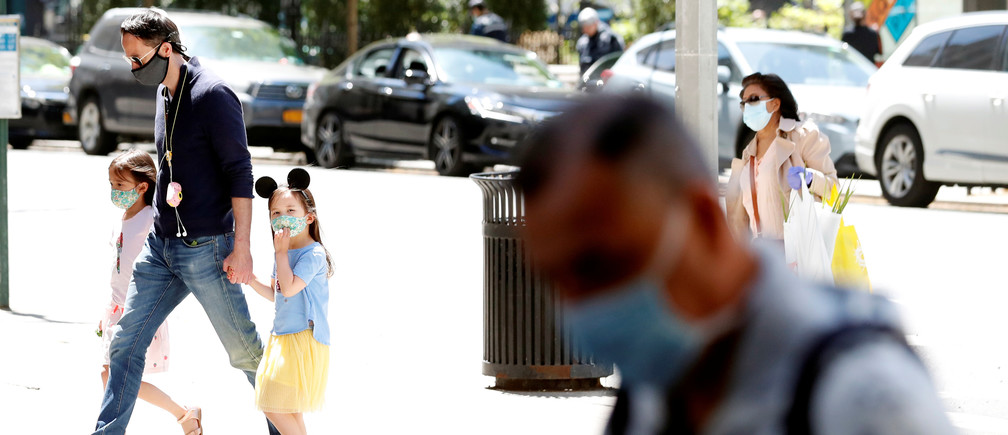 A man holds the hands of two young girls wearing masks as they cross the street as residents of New York City adjust to living with the ongoing outbreak of the coronavirus disease (COVID-19) in the Manhattan borough of New York U.S., May 20, 2020. REUTERS/Lucas Jackson - RC2LSG9DZMEL