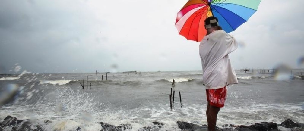 A fisherman holds an umbrella while watching his net as waves hit the Marunda beach in Jakarta February 1, 2007. Indonesia could lose about 2,000 islands by 2030 due to climate change, the country's environment minister said on Monday. A draft U.N. report due to be released in Paris on February 2 projects a big rise in temperatures this century and warns of more heat waves, floods, droughts and rising seas linked to greenhouse gases.  REUTERS/Beawiharta (INDONESIA) - GM1DUNARXHAA