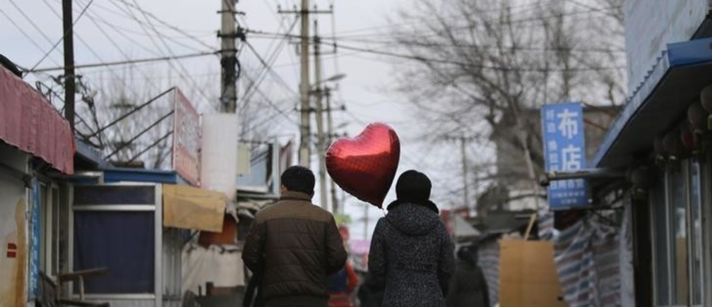 A woman holding a heart-shaped balloon walks with her partner at a residential area for migrant workers on Valentine's Day in Beijing February 14, 2013. REUTERS/Jason Lee (CHINA - Tags: SOCIETY TPX IMAGES OF THE DAY)