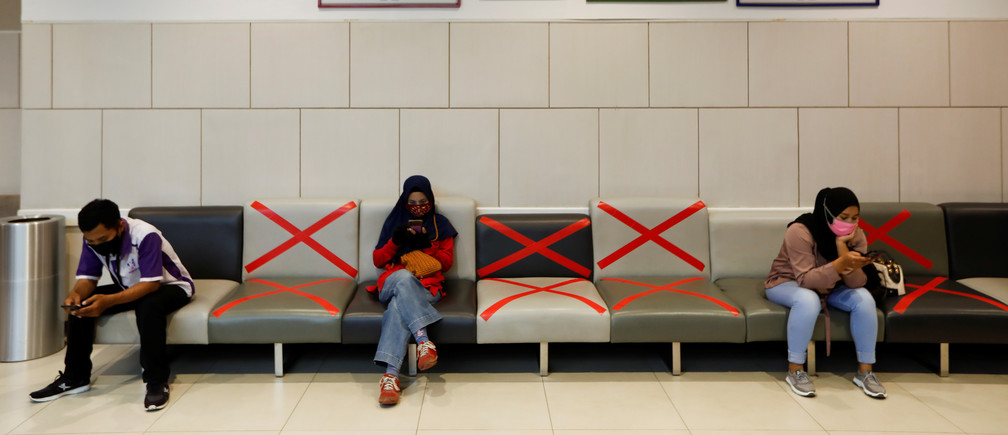 People wearing face masks use their phones while sitting inside a shopping mall amid the outbreak of the coronavirus disease (COVID-19), in Tangerang, on the outskirts of Jakarta, Indonesia, May 26, 2020. REUTERS/Willy Kurniawan - RC24WG9BJZBK