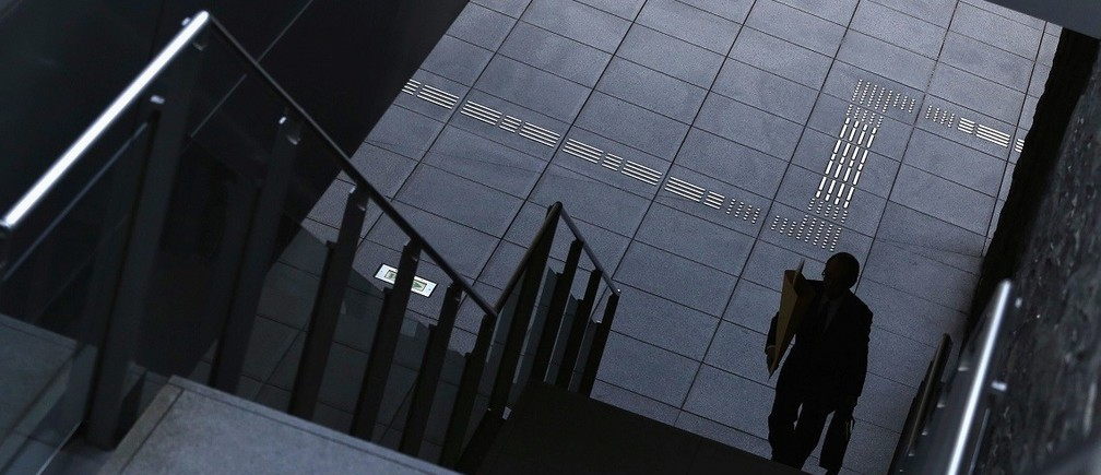 A man goes up the stairs at Tokyo's business district December 8, 2014. Japan's economy shrank more than initially reported in the third quarter on declines in business investment, data showed on Monday, surprising markets and backing premier Shinzo Abe's recent decision to delay a second sales tax hike. REUTERS/Yuya Shino (JAPAN - Tags: BUSINESS) - RTR4H2EQ
