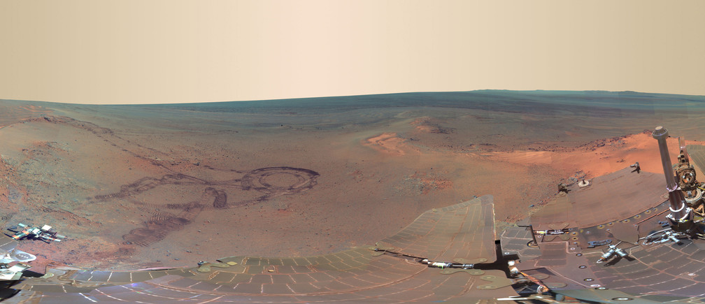This NASA 360-degree panorama image of Mars made from some of 800 images sent from the Opportunity rover on Mars shown in exaggerated colors to highlight different surface features released on July 9, 2012, shows past tracks of Opportunity (L) as well as Opportunity's dust covered solar panels cross the image bottom and an interior wall of 20-kilometer Endeavour Crater just below the horizon and right of center. Now that the northern Martian winter is over, Opportunity is rolling again, this time straight ahead (north). The rover is set to investigate unusual light-colored soil patches as it begins again to further explore the inside of Endeavour, a crater that may hold some of the oldest features yet visited.    REUTERS/NASA/JPL-Caltech/Cornell/Arizona State University/Handout  (UNITED STATES - Tags: ENVIRONMENT SCIENCE TECHNOLOGY) FOR EDITORIAL USE ONLY. NOT FOR SALE FOR MARKETING OR ADVERTISING CAMPAIGNS. THIS IMAGE HAS BEEN SUPPLIED BY A THIRD PARTY. IT IS DISTRIBUTED, EXACTLY AS RECEIVED BY REUTERS, AS A SERVICE TO CLIENTS - GM1E87A0KPY01