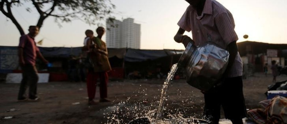 A boy fills a metal pitcher with water fetched from a communal tap at a slum in Mumbai, India, March 22, 2017.  REUTERS/Danish Siddiqui