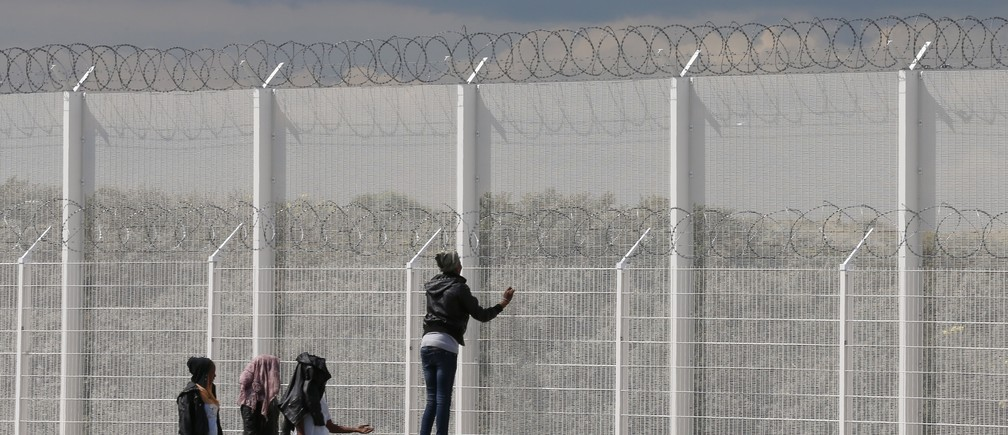 Migrants walk past the barbed wire fence on the main access route to the Ferry harbour Terminal in Calais, northern France, July 30, 2015.