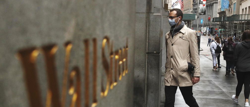 A man wears a protective mask as he walks on Wall Street during the coronavirus outbreak in New York City, New York, U.S., March 13, 2020. REUTERS/Lucas Jackson - HP1EG3D18FND0