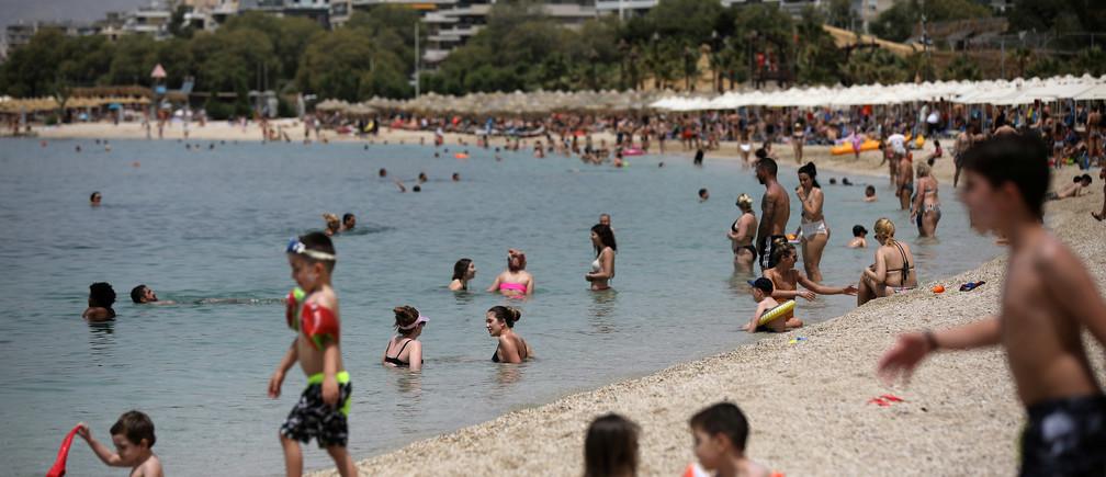 La gente disfruta del sol durante la reapertura oficial de las playas al público tras la flexibilización de las medidas contra la propagación de la enfermedad coronavirus (COVID-19), en Atenas, Grecia, el 16 de mayo de 2020.