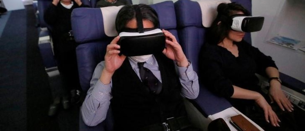 """Guests wearing virtual reality (VR) goggles are seen at the """"First Airlines"""", virtual first-class airline experience facility in Tokyo, Japan February 14, 2018. Picture taken February 14, 2018.  REUTERS/Toru Hanai"""