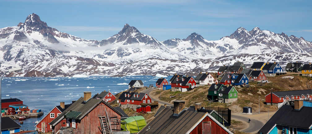 """Snow covered mountains rise above the harbour and town of Tasiilaq, Greenland, June 15, 2018. REUTERS/Lucas Jackson  SEARCH """"JACKSON TASIILAQ"""" FOR THIS STORY. SEARCH """"WIDER IMAGE"""" FOR ALL STORIES."""