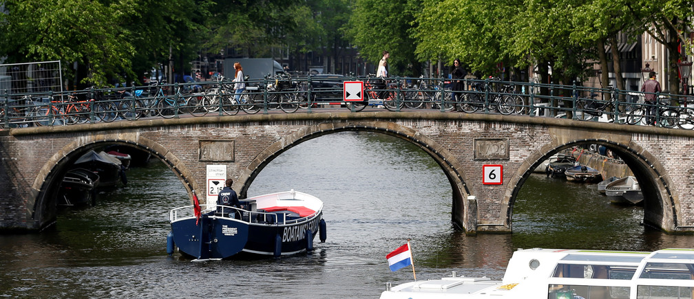 Tourists boats pass on a canal in Amsterdam, Netherlands, May 16, 2018. Picture taken May 16, 2018.  REUTERS/Francois Lenoir - RC1C45323F60