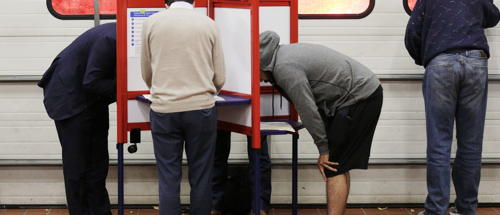 Voters look over their ballots at a fire station while a crew leaves on an emergency call during the U.S. presidential election in Arlington, Virginia, U.S., November 8, 2016.  REUTERS/Joshua Roberts - HT1ECB900D0DE
