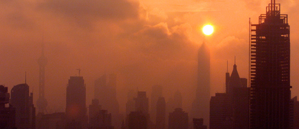The Shanghai skyline is silhouetted as the sun rises over China's business capital July 24, 2001