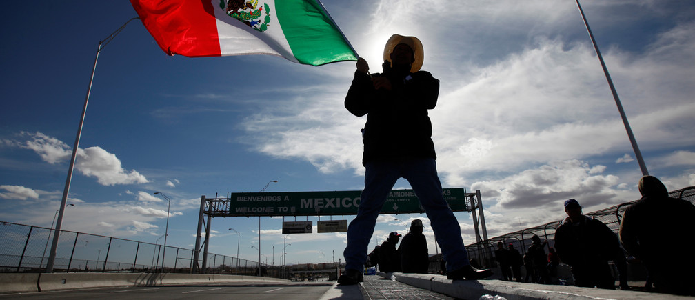 A farmer waves a Mexican flag while blocking the Bridge of the Americas border crossing between Ciudad Juarez, Mexico and El Paso, U.S., during a protest against a fuel price hike in Ciudad Juarez, Mexico January 20, 2017. REUTERS/Jose Luis Gonzalez
