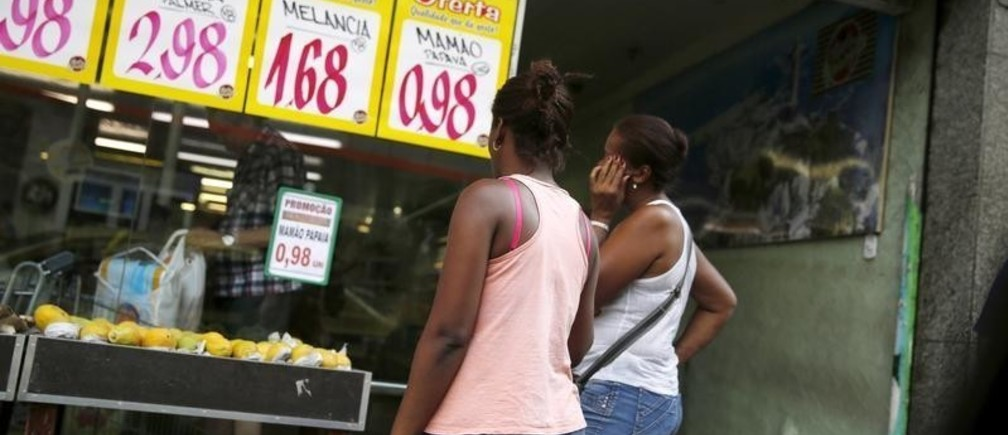 Women look at prices at a food market in Rio de Janeiro, Brazil, January 21, 2016. Brazil's real currency slipped to near its weakest ever against the U.S. dollar on Thursday as investors worried that erratic policy signals from President Dilma Rousseff may prolong a crippling recession in Latin America' biggest economy. REUTERS/Pilar Olivares - GF20000102653