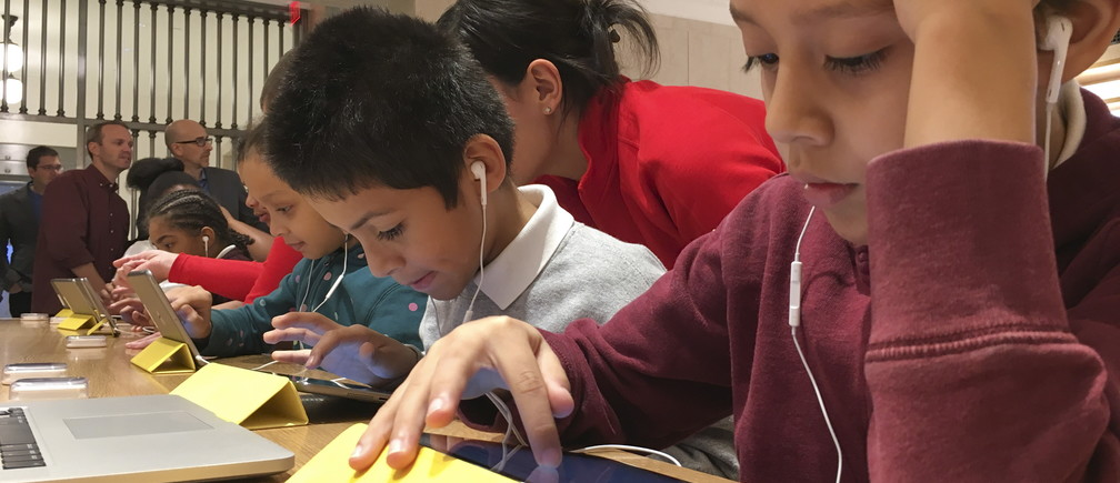 3rd grader Osiel Dominguez (R) attends an event for students to learn to write computer code at the Apple store in the Manhattan borough of New York December 9, 2015.     REUTERS/Carlo Allegri - GF10000260388
