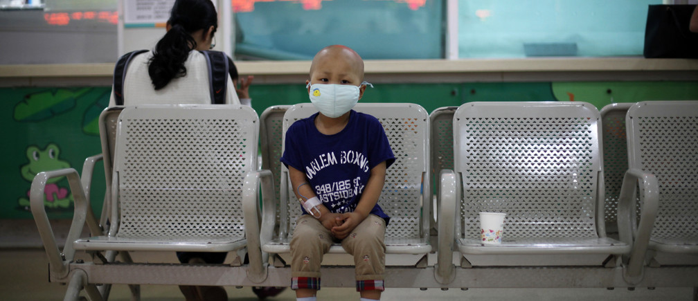Four-year-old Niuniu, who has late-stage neuroblastoma, a malignant cancer of the nervous system, sits on a bench while his mother pays his medical bills after getting tested for his fifth round of chemotherapy at Shanghai Children's Hospital May 2, 2013.