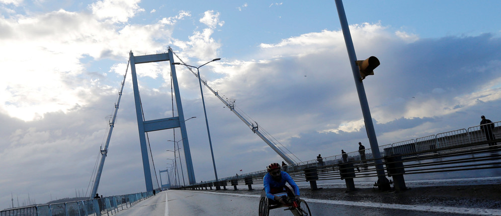 A participant taking part in the men's wheelchair division crosses the July 15 Martyrs' Bridge, known as the Bosphorus Bridge, which links the city's European and Asian sides, during the 38th annual Istanbul Marathon in Istanbul, Turkey, November 13, 2016. REUTERS/Murad Sezer - RTX2TF7U