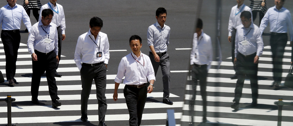 Office workers are reflected in a glass railing as they cross a street during lunch hour in Tokyo June 1, 2015.  REUTERS/Thomas Peter/File Photo                   GLOBAL BUSINESS WEEK AHEAD PACKAGE - SEARCH BUSINESS WEEK AHEAD SEPTEMBER 26 FOR ALL IMAGES - S1BEUDKRMPAA