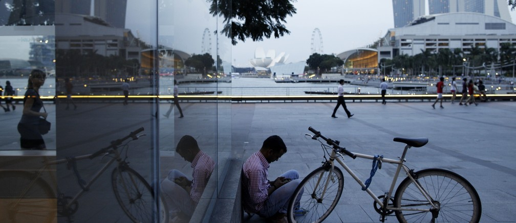 A migrant worker from India checks his mobile phone at the Marina Bay Promenade in the central business district of Singapore January 22, 2014.
