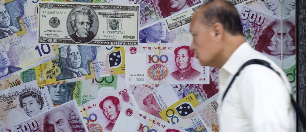 A man walks past an advertisement promoting China's renminbi (RMB) or yuan, U.S. dollar and Euro exchange services at foreign exchange store in Hong Kong, China, August 13, 2015. German Bund yields edged up on Thursday following efforts by China's central bank to slow a sharp descent of the yuan that has prompted investors this week to seek safe-haven assets. REUTERS/Tyrone Siu - GF10000172716