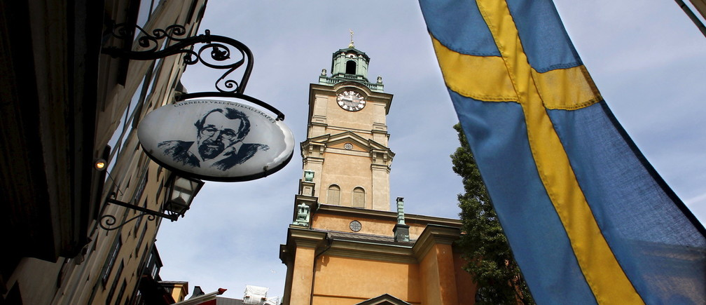Sweden's flag waves near the Stockholm Cathedral in Gamla Stan or the Old Town district of Stockholm, Sweden, in this June 9, 2010 file photo. REUTERS/Bob Strong/Files - RTX29ME7