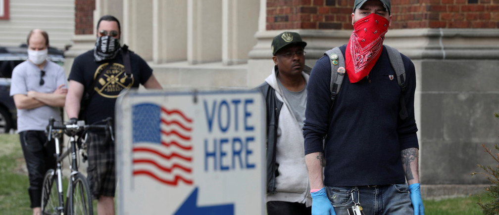 Patrick Kapple, right, waits in line outside Riverside University High School to cast a ballot during the presidential primary election held amid the coronavirus disease (COVID-19) outbreak in Milwaukee, Wisconsin, U.S. April 7, 2020. REUTERS/Daniel Acker - RC2XZF9P7TOM