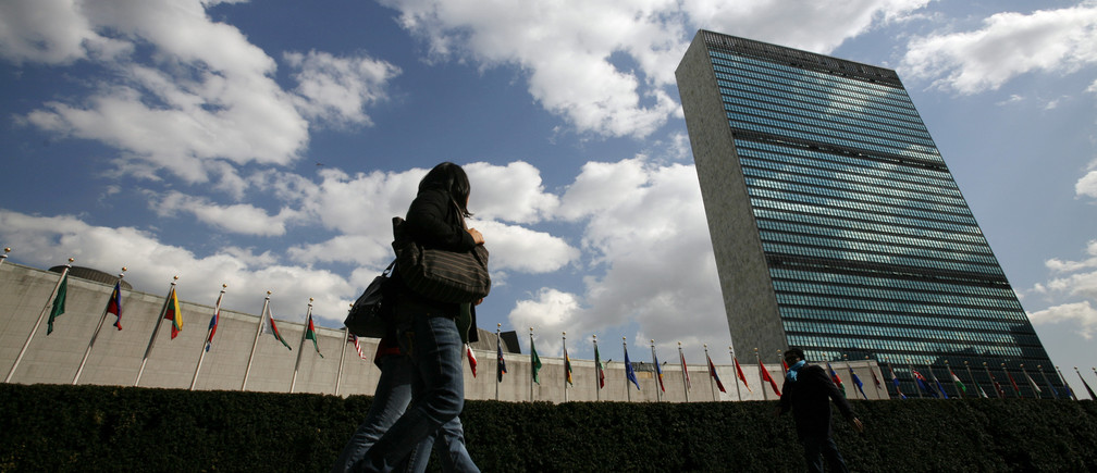 Tourists walk past the United Nations Headquarters in New York. At left is the U.N. General Assembly building and at right is the U.N. Secretariat building