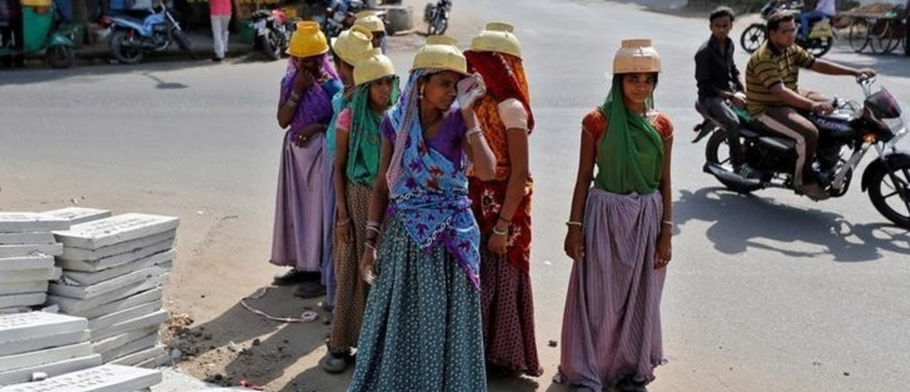 """Sarta Kalara (C), a construction worker, stands among other female workers in Ahmedabad, India, April 20, 2016. Kalara says she has no option but to tether her daughter Shivani to a stone despite her crying, while she and her husband work for 250 rupees ($3.8) each a shift digging holes for electricity cables in the city of Ahmedabad. There are about 40 million construction workers in India, at least one in five of them women, and the majority poor migrants who shift from site to site, building infrastructure for India's booming cities. Across the country it is not uncommon to see young children rolling in the sand and mud as their parents carry bricks or dig for new roads or luxury houses. REUTERS/Amit Dave       SEARCH """"TIED TODDLER"""" FOR THIS STORY. SEARCH """"THE WIDER IMAGE"""" FOR ALL STORIES       TPX IMAGES OF THE DAY"""