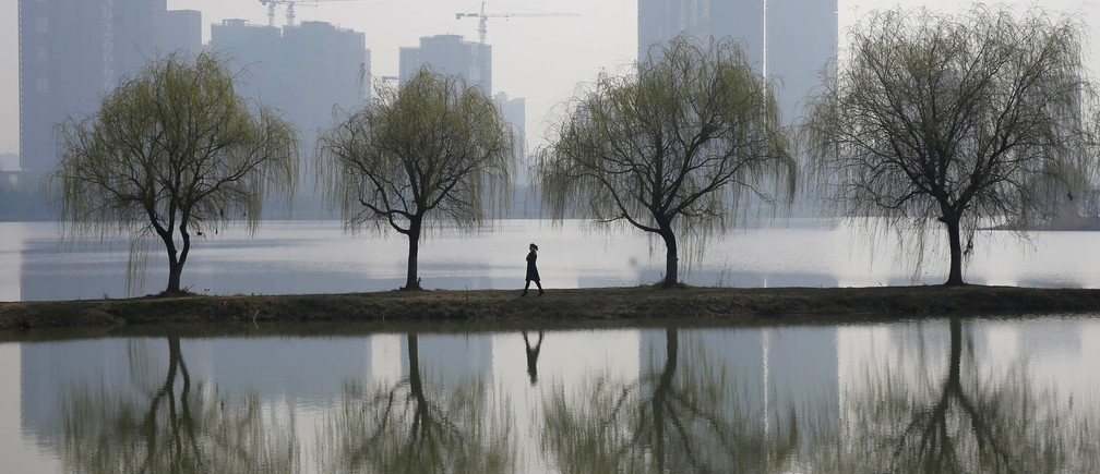 A woman walks past trees reflected on a lake in front of a construction site of a residential compound on a hazy day in Wuhan, Hubei province March 6, 2015.