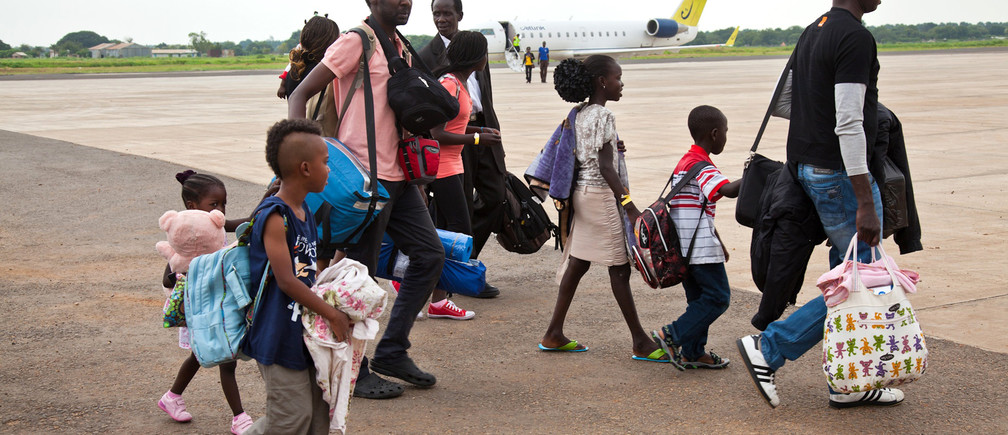 South Sudanese nationals who arrived from Israel walk from their plane at the airport in Juba June 18, 2012.