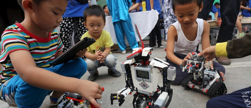 Children play with humanoid robots during a science promotional event in Zhengzhou, Henan province, September 19, 2015.