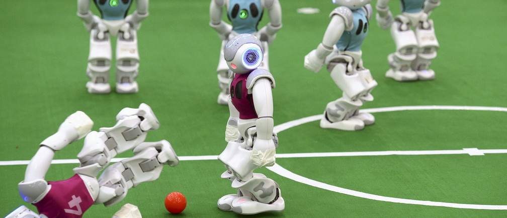 A robot falls as others compete in a soccer match at the RoboCup 2015, at an exhibition centre in Hefei, Anhui province, China, July 19, 2015. Over 2,000 people have registered to join the RoboCup in Hefei this year which will be held from July 19 to July 23, local media reported. REUTERS/Stringer CHINA OUT. NO COMMERCIAL OR EDITORIAL SALES IN CHINA    - GF10000163955