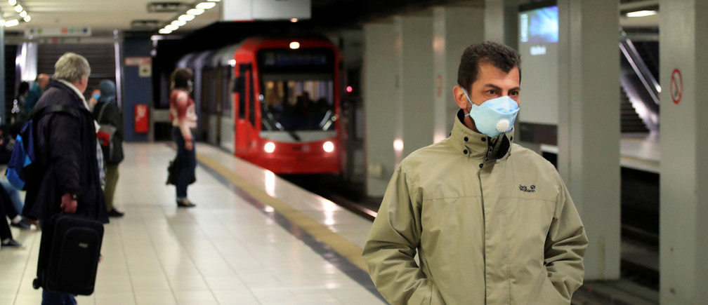 A commuter wearing a face mask stands at the Cologne main station after the federal state of North Rhine-Westphalia decided to make wearing protective masks obligatory in buses, trains and shops to fight the spread of the coronavirus disease (COVID-19), in Cologne, Germany, April 27, 2020. REUTERS/Wolfgang Rattay - RC2UCG9Z09Z2