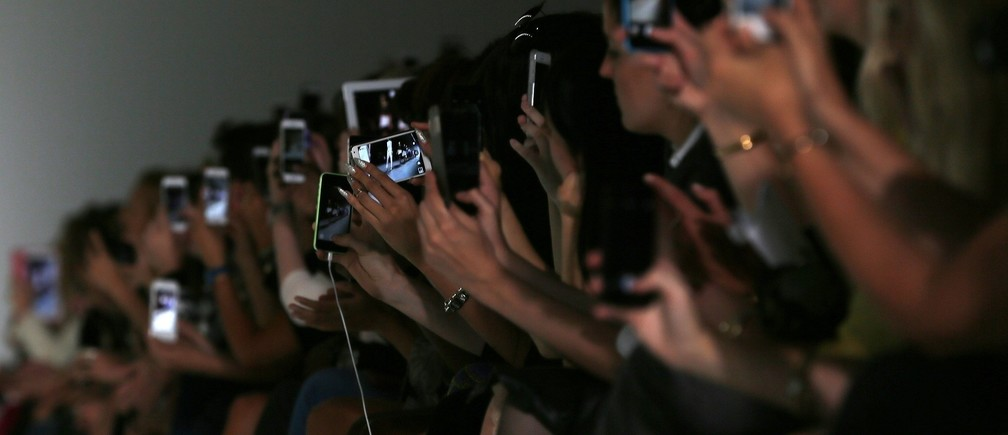 Guests use their mobile devices during the David Koma Spring/Summer 2015 collection presentation at London Fashion Week September 14, 2014. REUTERS/Stefan Wermuth (BRITAIN - Tags: FASHION) - RTR466NP