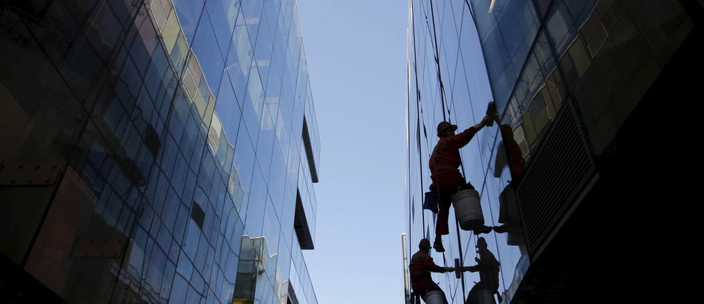 Workers clean windows of a shopping mall building in Beijing, October 30, 2015. China's Communist Party said on Thursday that it would target medium to high growth for the next five years, the official Xinhua news agency reported. REUTERS/Kim Kyung-Hoon TPX IMAGES OF THE DAY  - GF20000038486