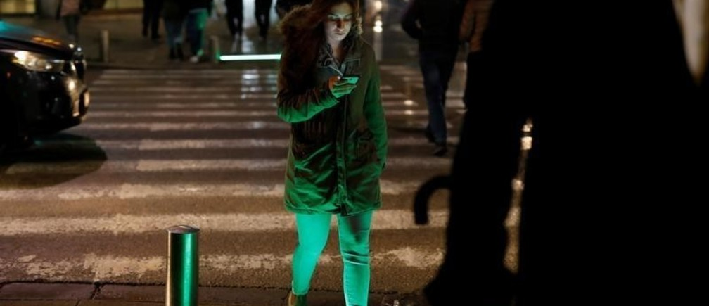 A pedestrian uses her smartphone as she crosses a road with newly installed ground-level crosswalk lights, in Tel Aviv, Israel March 14, 2019. REUTERS/Corinna Kern - RC1F44A03100