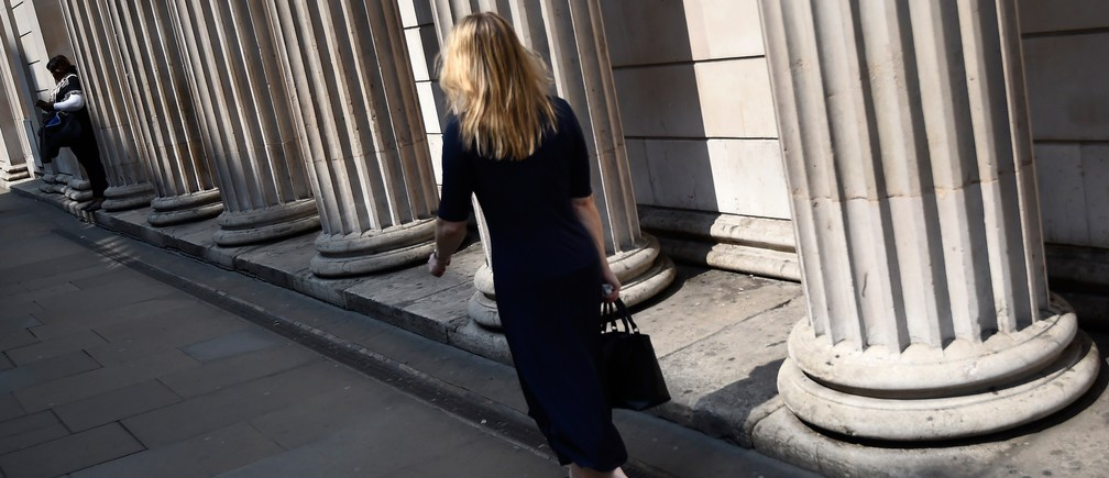 A woman walks past the columns outside the Bank of England in the City of London, Britain, May 12, 2016.