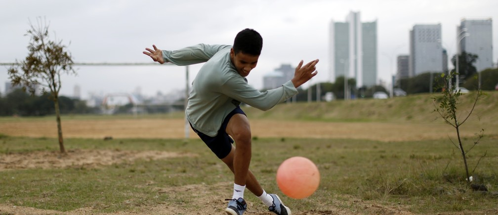 A boy plays soccer in a park in Porto Alegre June 16, 2014. In a project called 'On The Sidelines' Reuters photographers share pictures showing their own quirky and creative view of the 2014 World Cup in Brazil. REUTERS/Marko Djurica (BRAZIL - Tags: SPORT SOCCER WORLD CUP SOCIETY) - RTR3U5LF