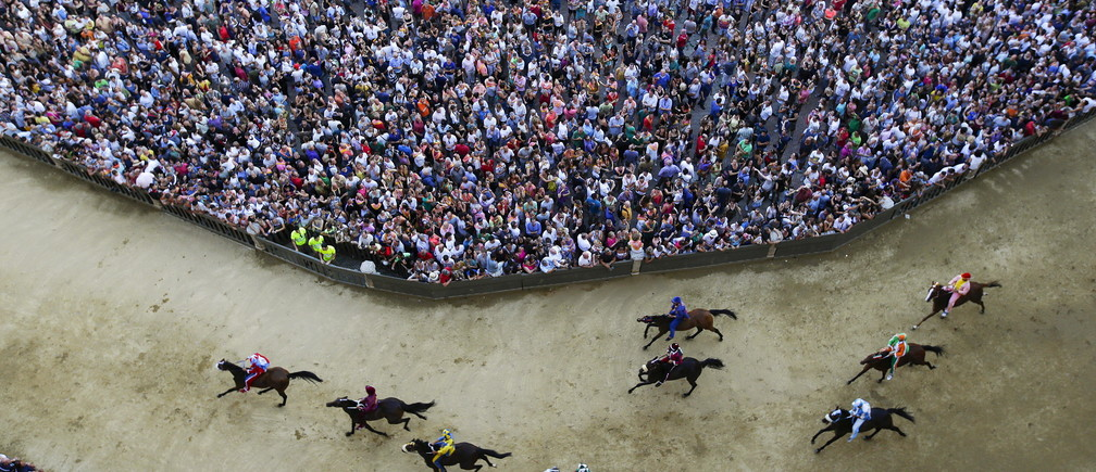 Horses race during the general practice session for the Palio di Siena horse race in Siena, Italy, July 1, 2015. Each July 2 and August 16, almost without fail since the mid-1600s, 10 riders have hurtled bareback around Siena's shell-shaped central square in a desperate bid to win the Palio, a silk banner depicting the Madonna and child. REUTERS/ Max Rossi TPX IMAGES OF THE DAY     ATTENTION EDITORS - FOR EDITORIAL USE ONLY. NOT FOR SALE FOR MARKETING OR ADVERTISING CAMPAIGNS.  - GF10000146023