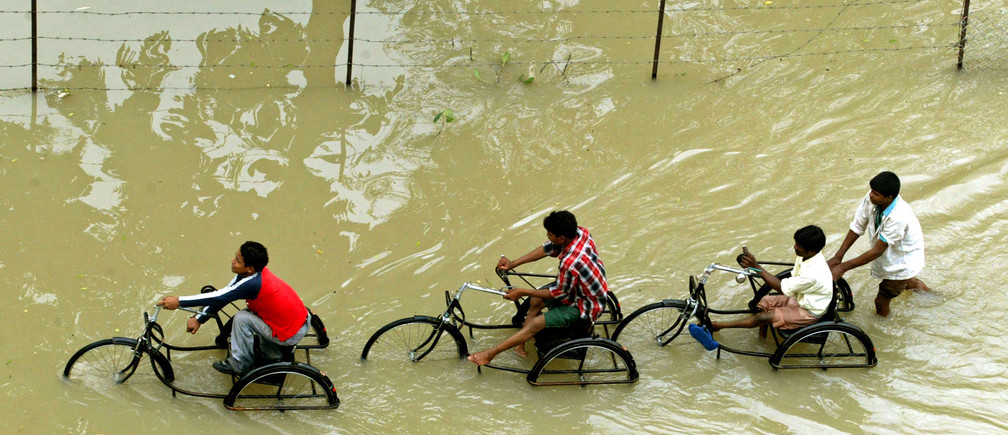Indian students cycle through a flooded street in Vadodara city, 116 km (72 miles) south of the western Indian city of Ahmedabad July 4, 2005. Indian military helicopters dropped food packets on Monday to thousands of people stranded in vast lakes of water in the west of the country as monsoon rains ebbed after flooding that killed 132 people. REUTERS/Amit Dave  VM/KI - RP6DRMUDLDAA
