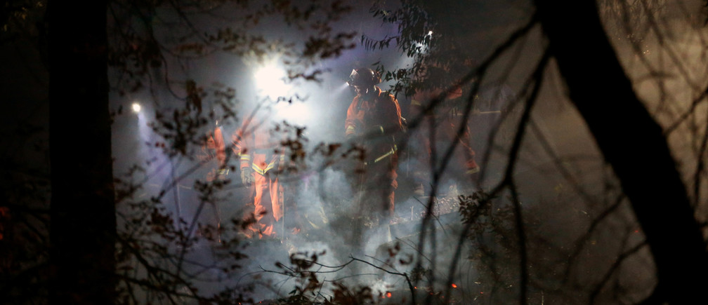 An inmate hand crew mops up hot spots along Wright creek during the Kincade fire in Healdsburg, California, U.S. October 28, 2019. REUTERS/Stephen Lam - RC1F55174190