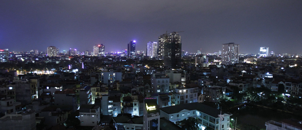 The skyline of Hanoi is seen from a building at night December 1, 2011. The country's population density is nearly 260 people for each square km, six times above the world's average, the local media said on Wednesday. REUTERS/Kham (VIETNAM - Tags: CITYSPACE SOCIETY) - GM1E7C2032C01