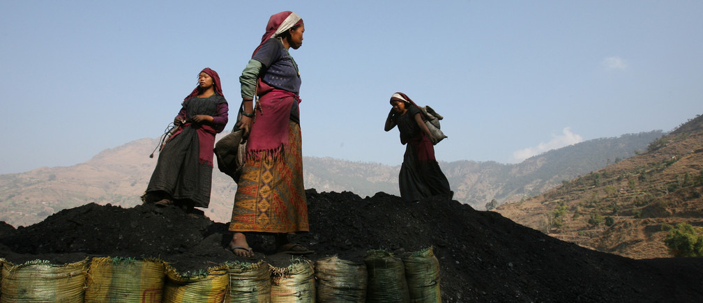Nepali miners unload sacks of coal near the village of Tila, Rolpa district, the heartland of Maoist insurgents in western Nepal, February 12, 2006. Aid agencies estimate at least 200,000 of Nepal's 26 million people are refugees. At least as many more have left their homes uncounted, many now living with relatives in crowded and impoverished cities or in slums. Millions have also been forced to head south to India in search of work, where they toil as labourers or household servants. Picture taken on February 12, 2006.  REUTERS/Desmond Boylan - GM1DRZALJQAA