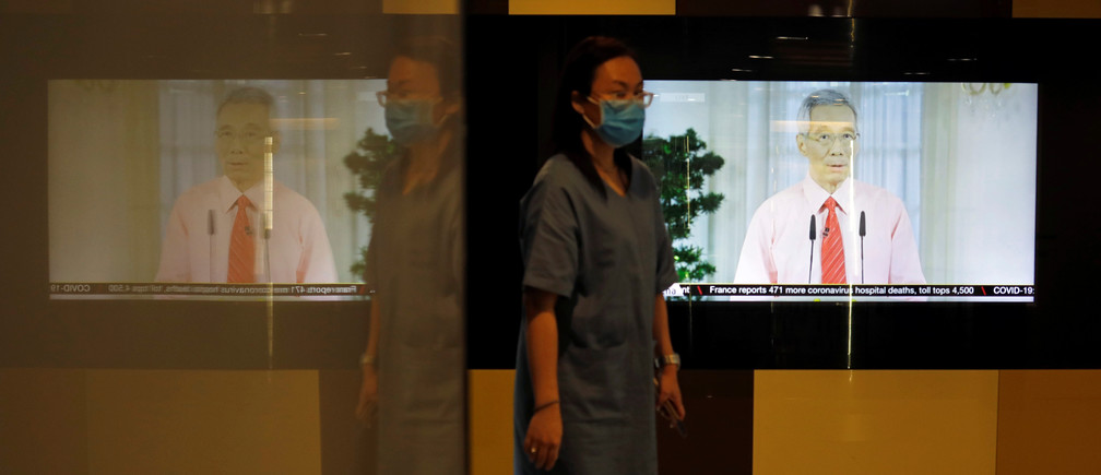 A woman with a face mask walks past a screen showing a telecast of Singapore's Prime Minister Lee Hsien Loong addressing the outbreak of coronavirus disease (COVID-19), at the central business district in Singapore, April 3, 2020.